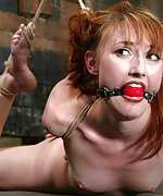 Latex redhead gets roped, ball-gagged and tortured
