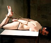 Mindy hard hogtied, ball-gagged on the table
