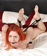 Redhead roped naked and hogtied on the bed